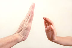 Child`s hand try to touch senior hand  or old woman hand. select Stock Photography
