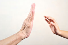 Child`s hand try to touch senior hand  or old woman hand.selecti Stock Images