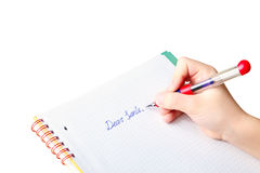 Child's hand writing letter to Santa Claus Stock Photo