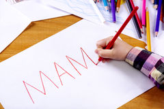 Child's hand is writing MAMA. Child's hand with the red pencil writing MAMA on a white sheet of paper Royalty Free Stock Photos