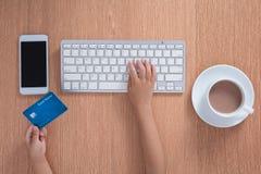 Child& x27; s handen die creditcard houden en op toetsenbord typen stock foto