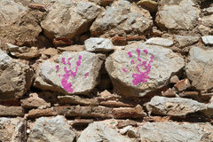 Child's handprint on stone wall. In pink paint Stock Photos