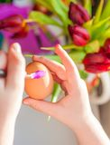 Child`s hands decorating an easter egg. Negative space. stock photo