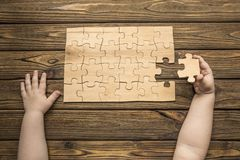 The child`s hands collect a puzzle on the background of a wooden table. Development, educatio n royalty free stock image