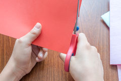 Child`s hands cutting colored red paper with scissors Stock Photos