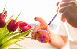 Child`s hands decorating Easter egg. Negative space. stock photo