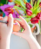 Child`s hands decorating Easter egg. Negative space. stock photography