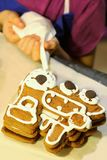 Child`s hands decorating gingerbread Christmas train at home kitchen. Table Royalty Free Stock Photo