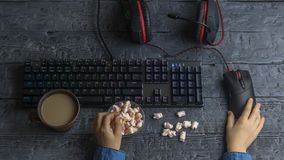 Girl eating colored marshmallows sitting at the gaming computer. The view from the top. The child`s hands in a denim shirt playing the keyboard on the Desk with Stock Image