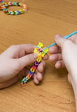 The child's hands doing a bracelet Royalty Free Stock Photos
