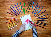 Child`s hands drawing a flower on a notebook with color pencils on the wooden table Stock Image