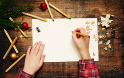 Child`s hands on the empty clean sheet of paper, pencils and Christmas decorations Royalty Free Stock Photo