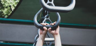 Child`s hands gripping playground equipment. Closeup shot of a child`s hands climbing on playground metal rights Stock Photos