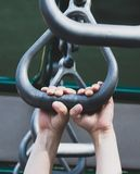 Child`s hands gripping playground equipment. Closeup shot of a child`s hands climbing on playground metal rights Stock Photo
