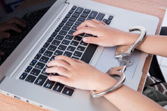 Child& x27;s hands in handcuffs with laptop Stock Photo