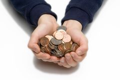 Child's hands holding coins. A child's hands holding a variety of coins isolated on white Stock Photo