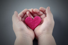 Child's hands holding the cracked pink heart Royalty Free Stock Photography