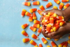 Child`s hands holding Halloween candy corn, selective focus. Child`s hands holding halloween candy corn Royalty Free Stock Photos