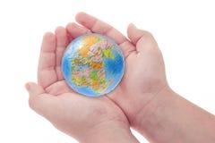 Child's hands holding jigsaw puzzle globe. On white background Stock Image
