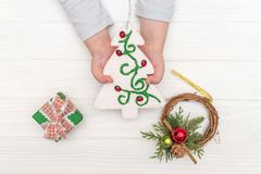 Child`s hands holding ornamental christmas tree near gift boxes on white table Stock Photo