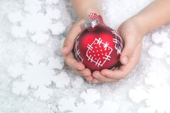 Child holding red patchwork Christmas bauble on white stock photography