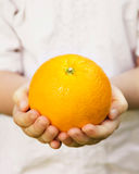 Child's hands holding ripe orange Stock Image