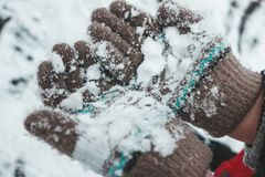 Child`s hands in knitted woollen gloves in snow. royalty free stock photos