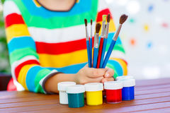 Child's hands with lots of brushes and colorful watercolors. Closeup of child's hands with lots of brushes and colorful watercolors. Kid preparing stationary and Royalty Free Stock Photos
