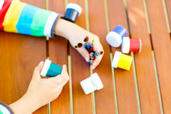 Child's hands with lots of brushes and colorful watercolors stock images