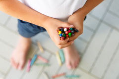 Child`s hands with lots of colorful wax crayons Stock Photography