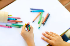 Child`s hands with lots of colorful wax crayons Stock Images