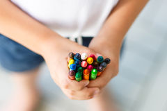 Child`s hands with lots of colorful wax crayons Stock Image