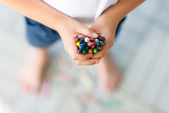 Child's hands with lots of colorful wax crayons Royalty Free Stock Photo