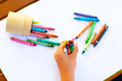 Child's hands with lots of colorful wax crayons Stock Photo