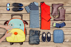 Child`s hands moving a suitcase next to clothes on the floor. A picture of traveling inventory of a child and personal belongings laid out clothes, shoes Royalty Free Stock Image