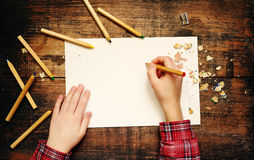 Child`s hands over empty white the sheet of paper and wooden colored pencils on the made old wooden surface Royalty Free Stock Image