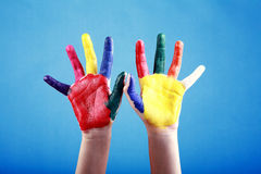 Child's hands painted with multicolored finger paints. On blue background Royalty Free Stock Images