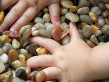 Child's hands in pebbles Stock Image