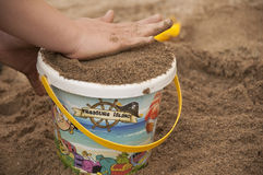 Child's hands and plastic colorful bucket with sand Royalty Free Stock Photo
