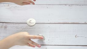 The child`s hands are playing with bitcoin coins on a wooden table. The child plays with a crypto currency. Slow motion stock footage