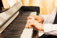 Child's hands playing on the piano-keys Stock Images