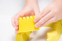 A child`s hands playing with yellow magic sand and building, kne. Ading at home. Preschool and school game, educational toy that can be used during family plays royalty free stock photo