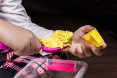 A child`s hands playing with yellow magic sand and building, kne. Ading at home. Preschool and school game, educational toy that can be used during family plays stock photo