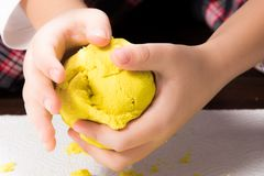 A child`s hands playing with yellow magic sand and building, kne. Ading at home. Preschool and school game, educational toy that can be used during family plays stock images