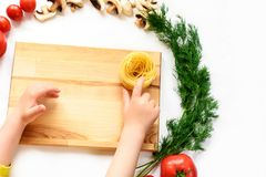 Child`s hands touching the pasta nest on a wooden desk, vegetables royalty free stock photography