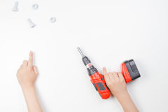 Child`s hands on white background. Boy pointing finger up and holding toy drill. Stock Photos