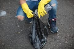 Child`s hands in yellow latex gloves holding a black garbage bag on an asphalt background. Ecology protection concept. A close-up picture of child`s legs and stock photos