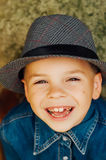 Child's happy face . Portrait of a Cute Kid. little boy with sh. Ort blond hair and brown yeas. Beautiful little boy seven years posing with a hat and denim stock photo