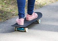 Child& x27; s iść na piechotę na deskorolka na asfaltowej drodze w parku zdjęcie royalty free