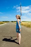 A child's journey. A young girl on a long walking journey with a tall stick.  She is on an empty road endlessly stretching under a bright blue sky Royalty Free Stock Images